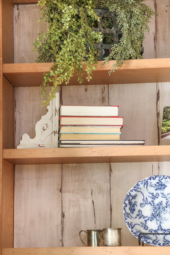how to decorate a bookcase by turning books around so you see the white pages.