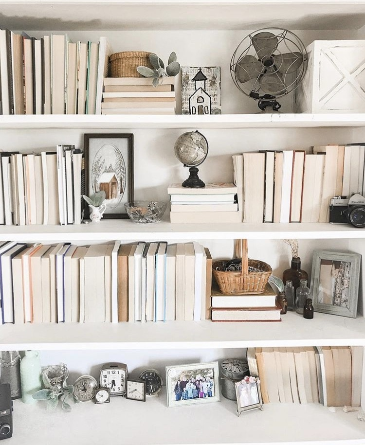 DIY Bookshelf Makeover by Samantha McGlothin with a full bookcase and clocks and vintage fan