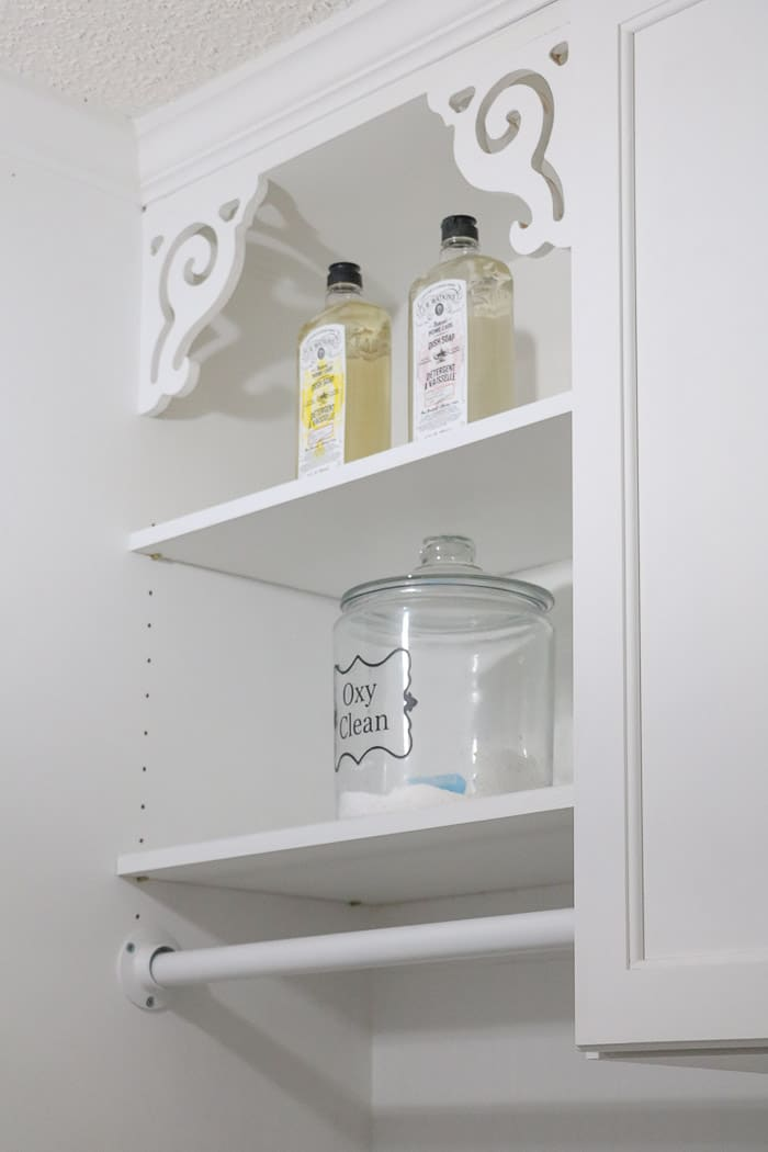 Small laundry room makeover using pretty soap bottles and jars for detergent on open shelves.