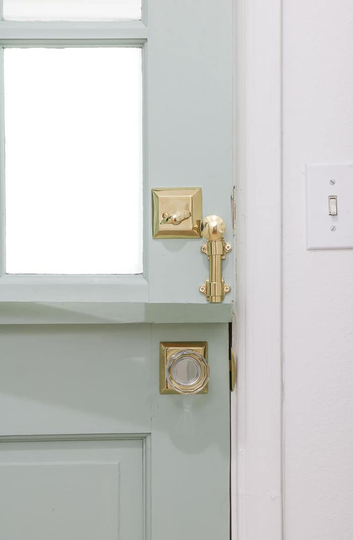 Small laundry room makeover using a dutch door and gold glass knob door hardware.