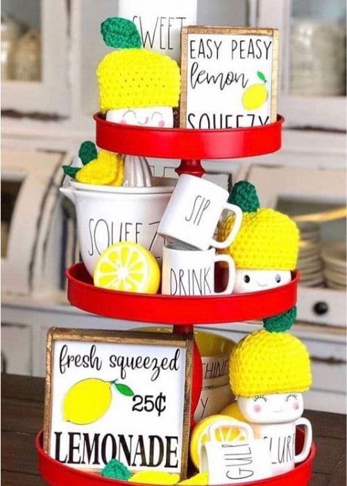 Lemon Décor by Little Cajun House with a red tiered tray filled with Rae Dunn, marshmallow cups, wood signs and lemons