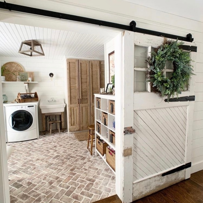 Farmhouse Laundry Room Decor by Love Homemade Home with a sliding farm door and brick flooring