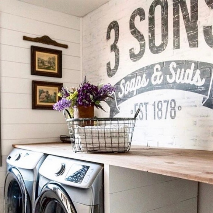 Farmhouse Laundry Room by Three Sons Farmhouse with painted bricks with a logo and a floating shelf