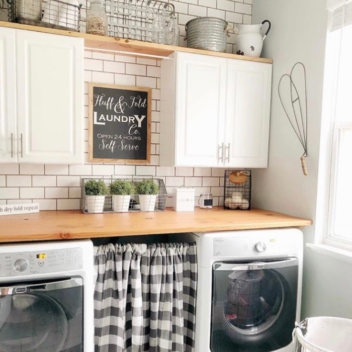Farmhouse Laundry Room Decor by Gnarled Knot with fluff and fold laundry signs and cabinets
