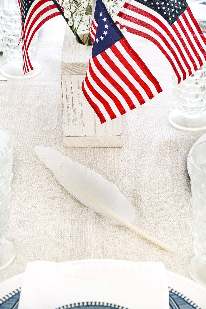 4th of July tablescape with Betsy Ross flags, drop cloth table runner, currier and ives dishes, cloth dinner napkins and red and white ribbon and babies breath
