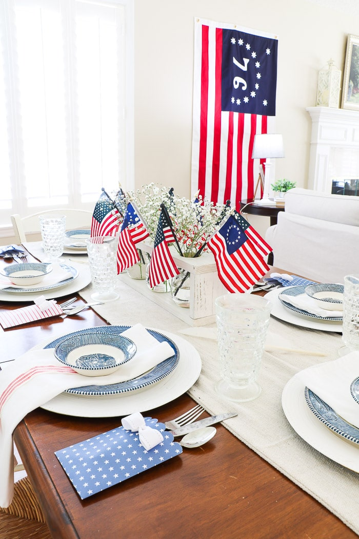 4th of July tablescape with Betsy Ross flags, drop cloth table runner, currier and ives dishes, cloth dinner napkins and red and white ribbon and babies breath.  Blue and white pillow cushions on  the bench and a Bennington flag.