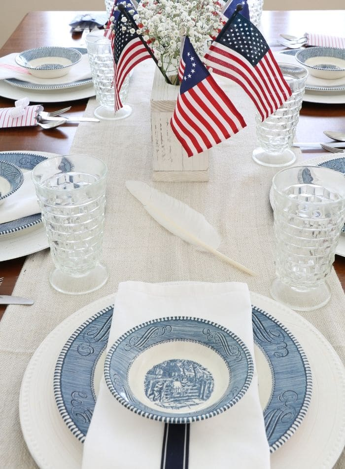 4th of July tablescape with Betsy Ross flags, drop cloth table runner, currier and ives dishes, goose quill pen and babies breath