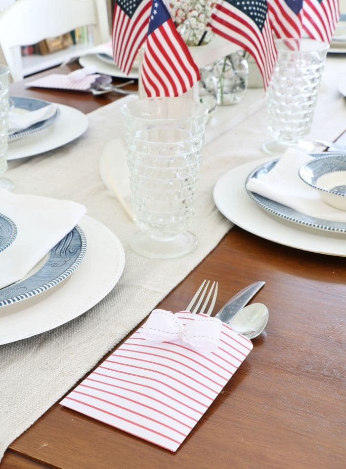 4th of July tablescape with Betsy Ross flags, drop cloth table runner, currier and ives dishes and babies breath
