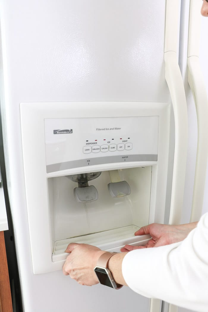 Clean fridge water dispenser by removing the tray and washing the tray.
