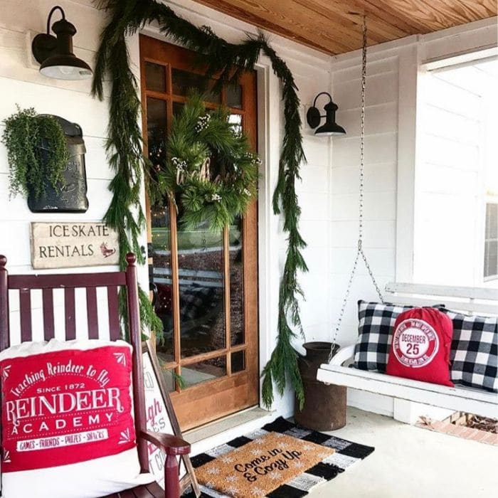 Layered Rug Ideas by 2561 Farmhouse with a Christmas styled front porch that includes a layered rug.  A doormat that says Come in and Cozy up laying on top of a black and white buffalo check rug.