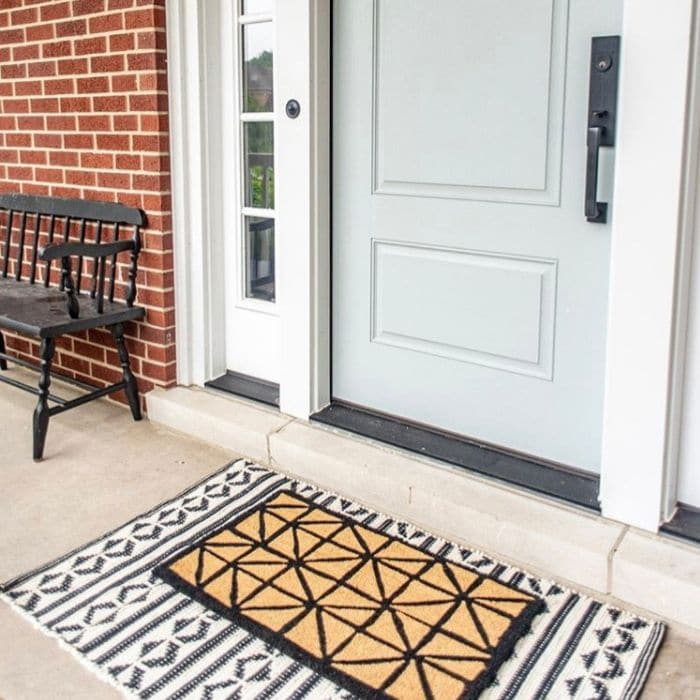 Layered Rug Ideas by Melissa Mahoney with a geometric rug layered under a geometric doormat