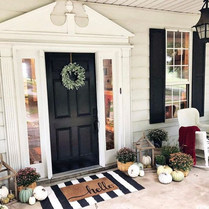 Layered Rug Ideas by Morgan Miller Blog with a hello doormat over a black and white stripe rug.
