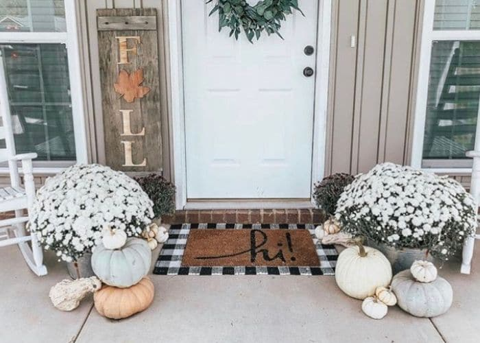 Layered Rug Ideas by Kristen Fortier with a doormat that says hi laying on top of a black and white gingham rug.