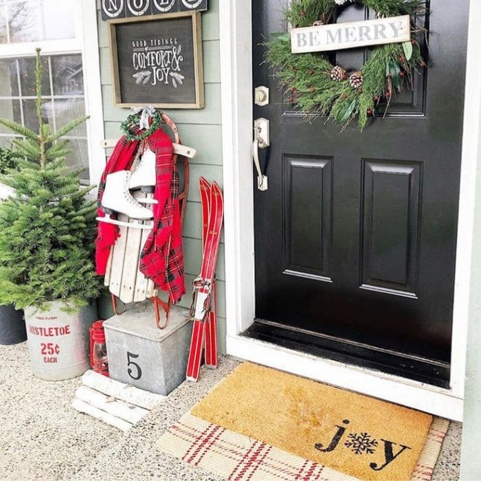 Layered Rug Ideas by Nesting Blissfully Interiors with a layered rug on a Christmas porch.  Layering a doormat that says joy over a red and white plaid rug.