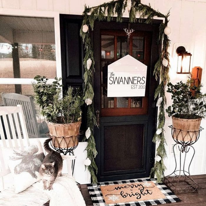 Layered Rug Ideas by Our Home Life with a Christmas porch decor idea using a doormat that says merry and bright layered over a black and white gingham rug.