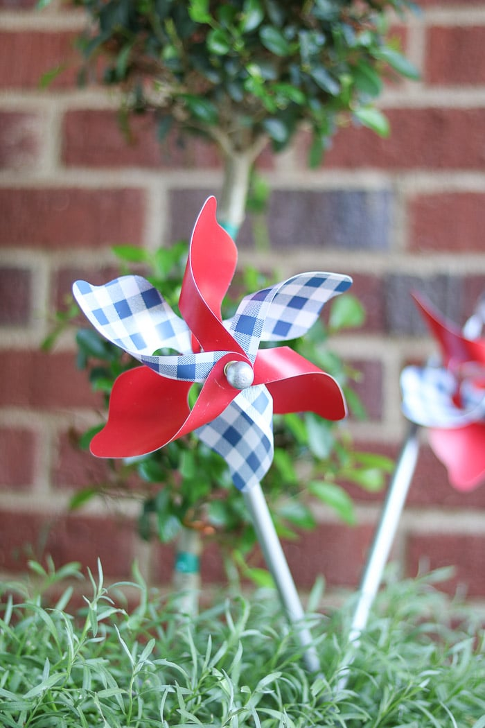 red, white and blue decorations on a small front porch for the 4th of July using a pinwheel