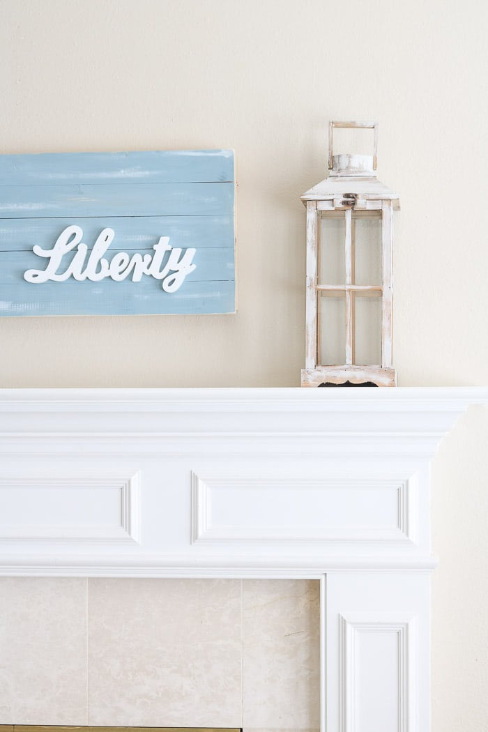 red, white and blue decorations on the mantle with a chambray blue shiplap wood art piece that has liberty wood cutout on it.