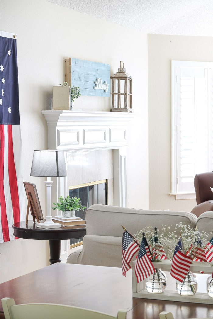 red, white and blue decorations on the mantle with a chambrey blue shiplap wood art piece that has liberty wood cutout on it.