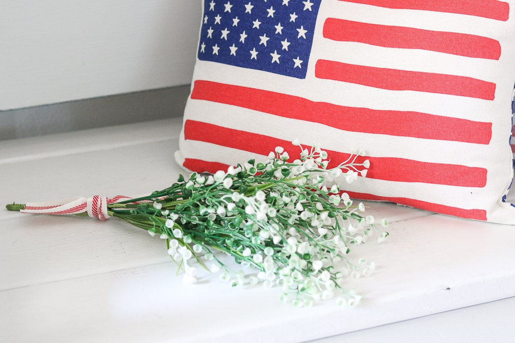 red, white and blue decorations in the entryway with American flag pillow and flowers