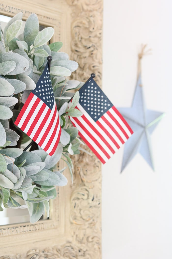 red, white and blue decorations in the entryway with American stick flags in a lambs ear wreath