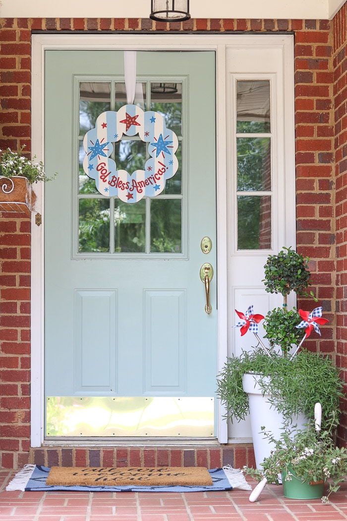 red, white and blue decorations on a small front porch for the 4th of July