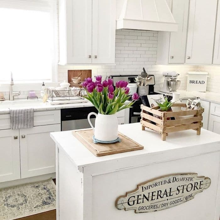 Farmhouse Kitchen with a sign on the kitchen island by French Coastal Home