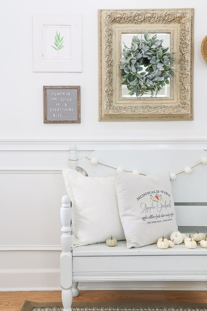 How to hang a gallery wall tutorial and decorating for fall by sitting pillows on a bench with small pumpkins and a picnic basket on the floor.