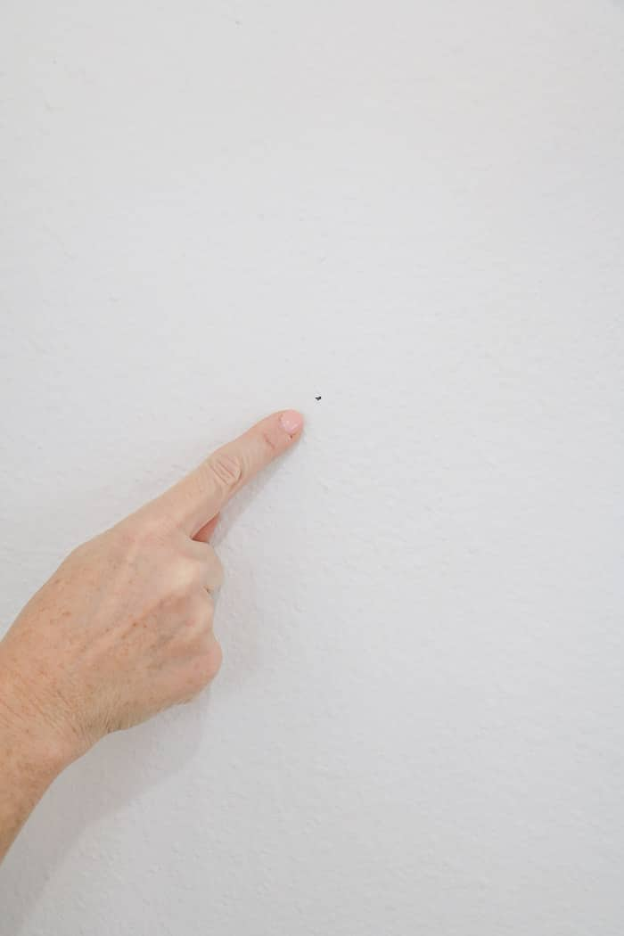 How to hang a gallery wall showing where your mark is for when you hammer the nail.