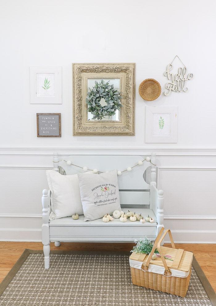 The finished room in this how to hang a gallery wall tutorial.  This vignette has two botanical free printables, mirror with lambs ear wreath over it, hello fall laser cut letters, letter board with pumpkin spice and everything nice on it, a basket, fall pillows, small pumpkins, picnic basket and flowers on the basket.