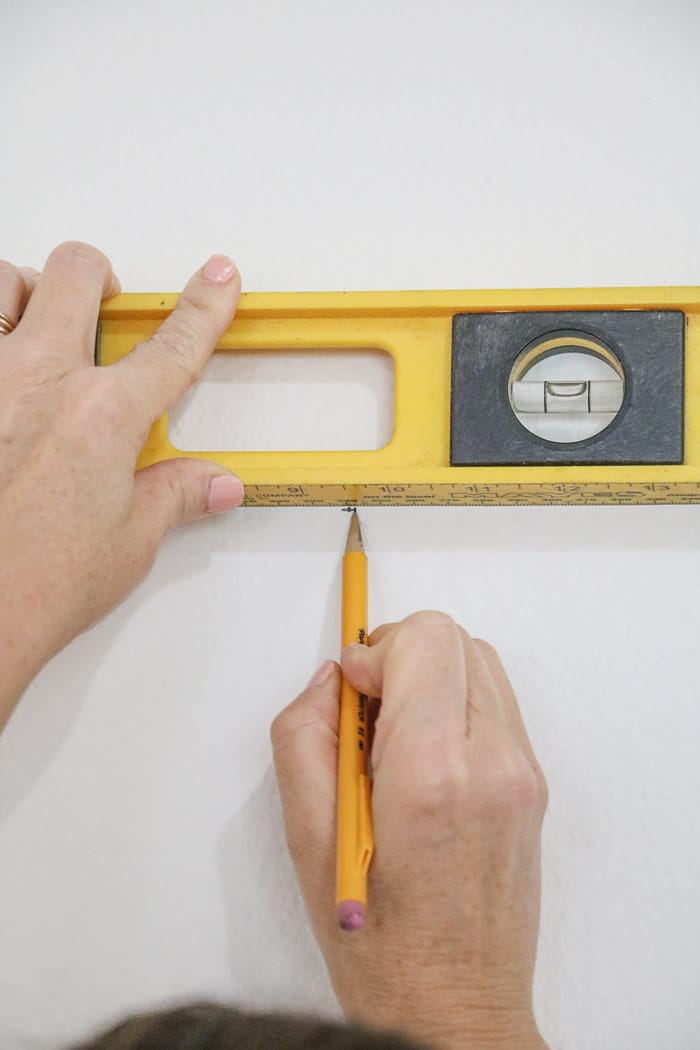 How to hang a gallery wall showing how to level for the nails.