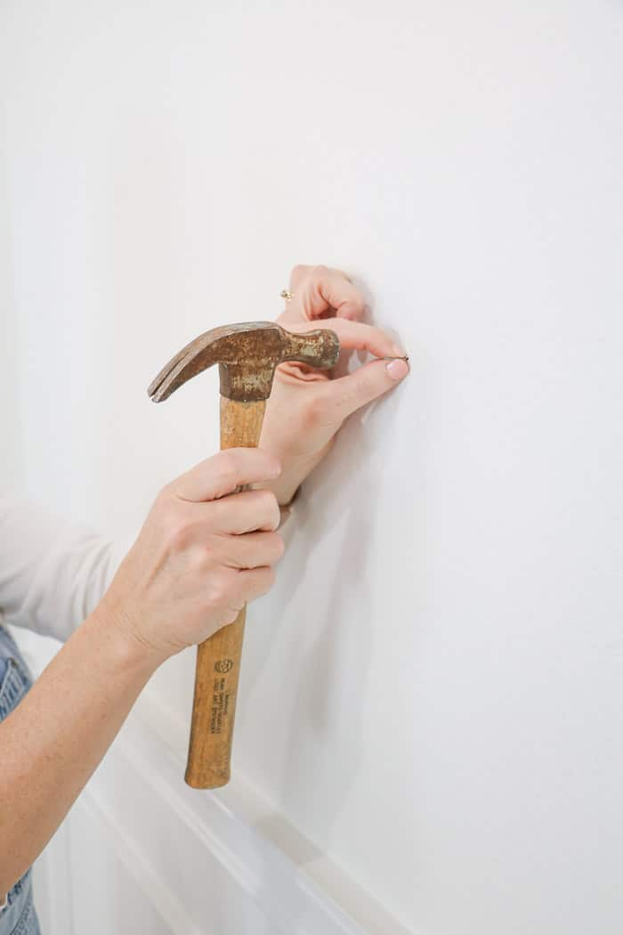 How to hang a gallery wall showing how to hammer a nail into the wall.