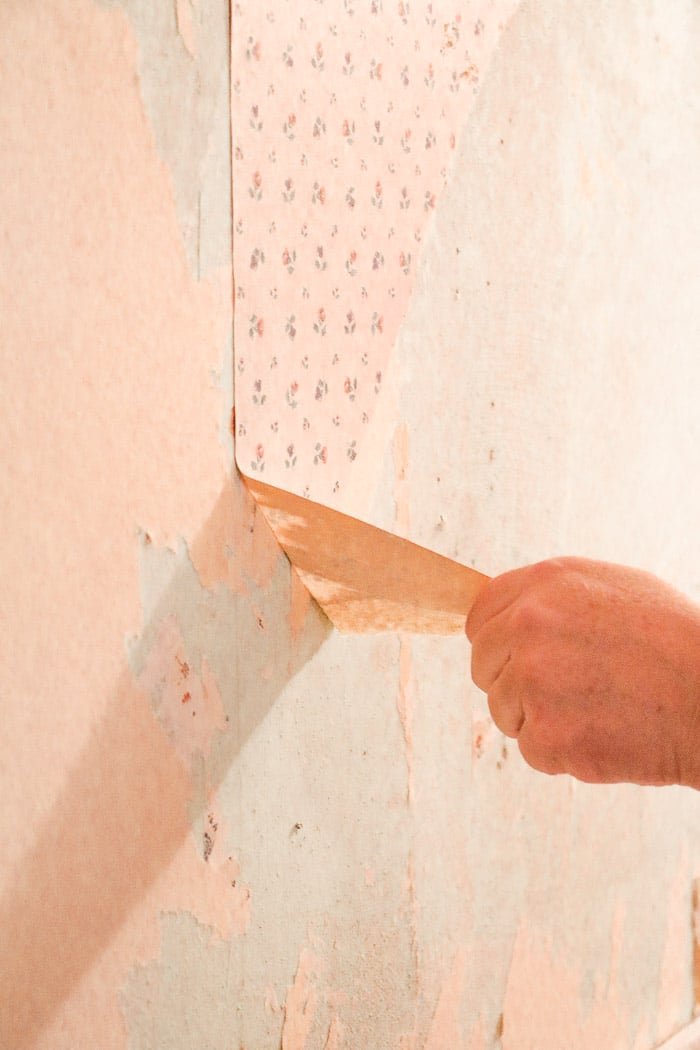 how to remove wallpaper with a steamer.  Removing old wallpaper starting by pulling the top layer of the wallpaper