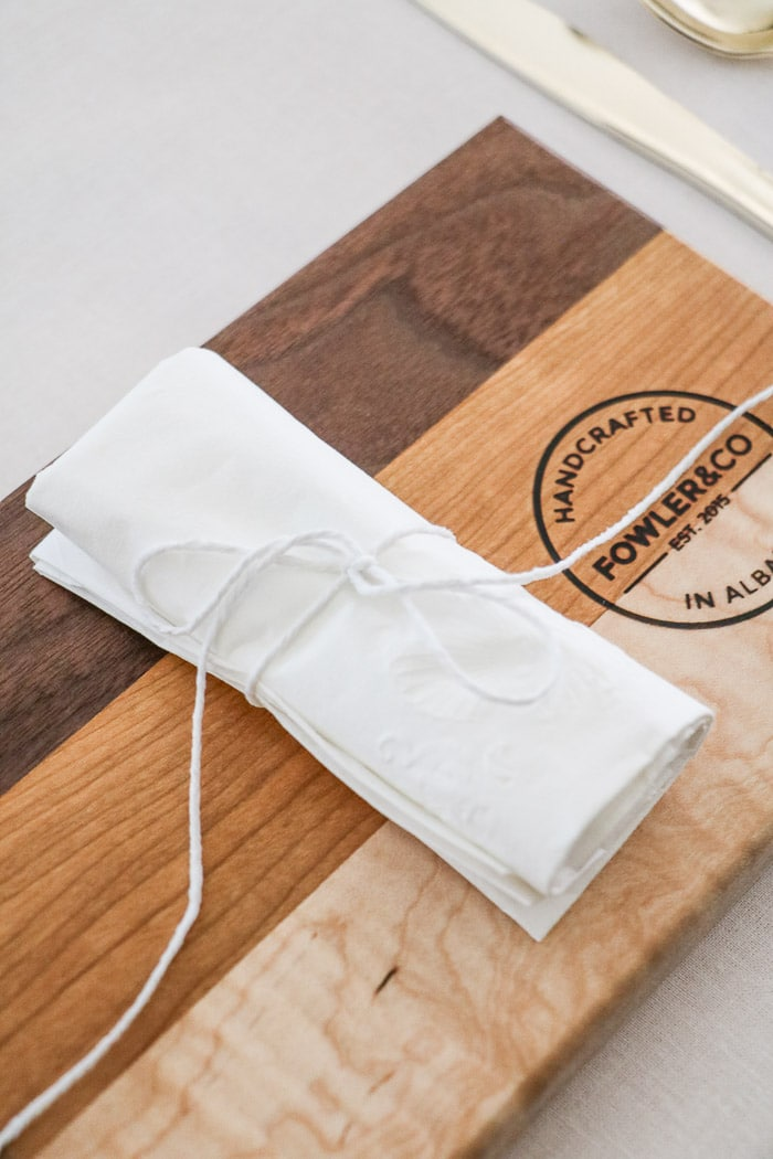 Nurses graduation party ideas.  Place cutting boards at each place setting as plates and top with a rolled napkin that is secured with white twine with long tails
