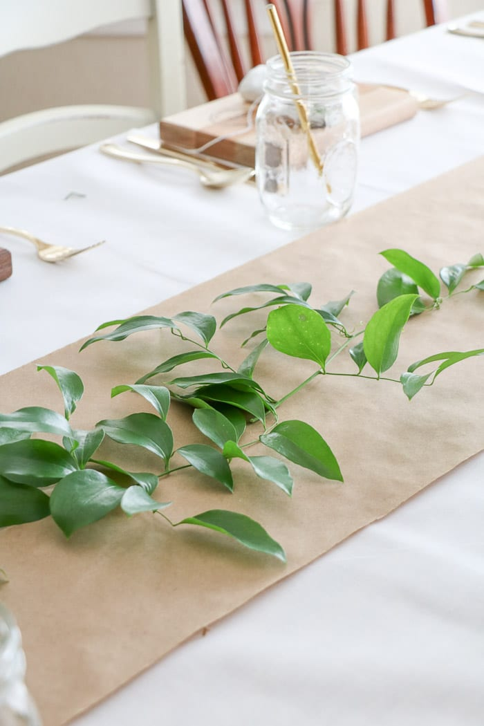 Adding a greenery called smilax that was gathered in the woods along the craft paper runner down the table.  Easy and cheap ideas for nurses graduation party ideas.