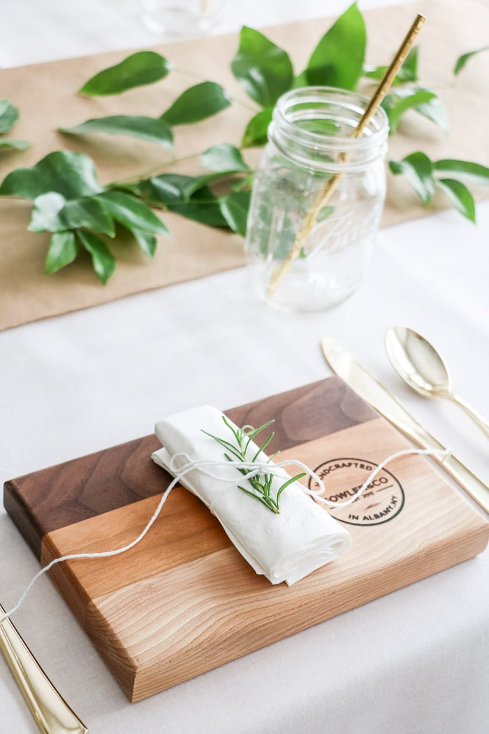 Nurses graduation party ideas that are casual and elegant.  Using Ball mason jars for glasses, cutting boards as plates, rolled napkin with rosemary tucked under twine that is holding the napkin together.  All creates a place setting for each guest.