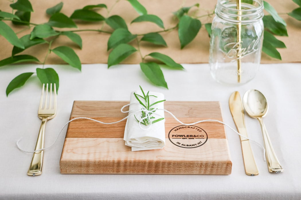 Nurses graduation party ideas that are casual and elegant.  A DIY sharing easy tips and trick for creating a special event. This place setting includes a cutting board as a plate. A rolled paper napkin that is tied with twine and rosemary tucked under the twine.  A glass Ball mason jar with a gold straw and all placed on a white tablecloth.