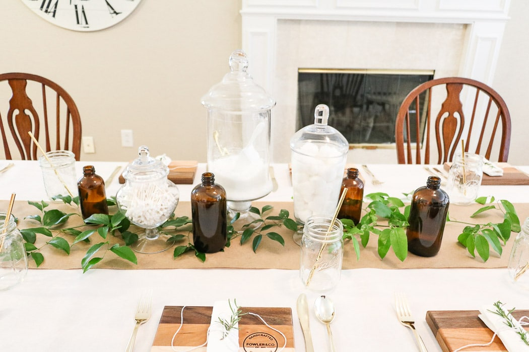 Adding a greenery called smilax that was gathered in the woods along the craft paper runner down the table.  Easy and cheap ideas for nurses graduation party ideas.  And add amber jars to the apothecary centerpiece for a more vintage medicinal vibe.