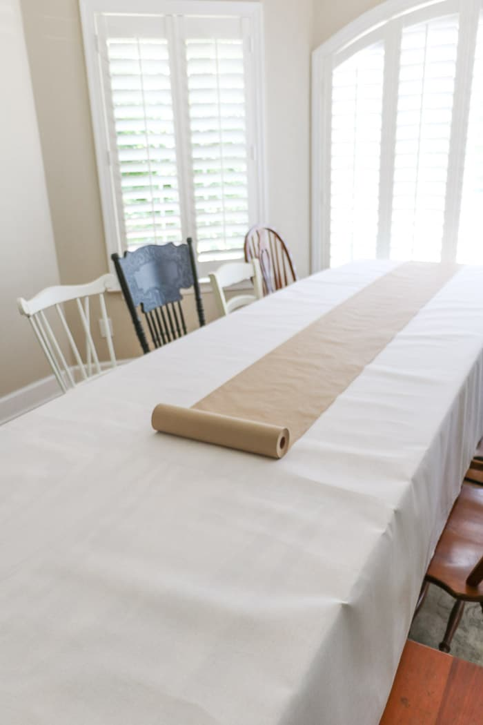 Nurses graduation party ideas using cut by the yard white fabric and brown craft paper for an extra long table.