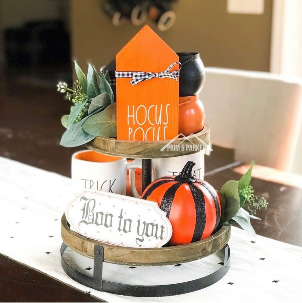 Halloween tiered tray ideas for home.  Orange Hocus Pocus house with black and white gingham ribbon bow, signs, Rae Dunn mug, pumpkin.
