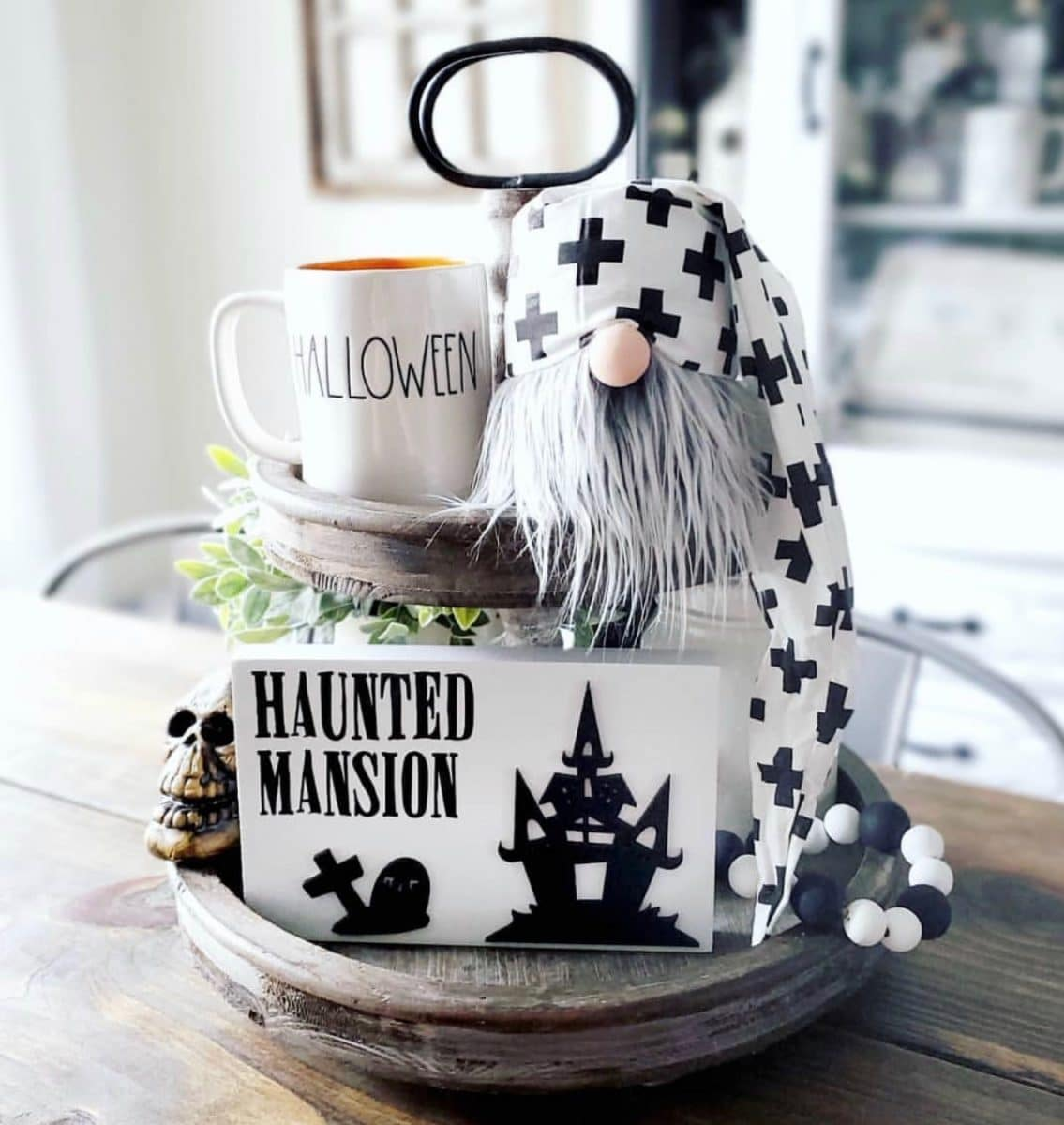 Halloween tiered tray ideas for home.  Gnome, Halloween Rae Dunn mug, haunted mansion sign, black and white wood beads, skeleton
