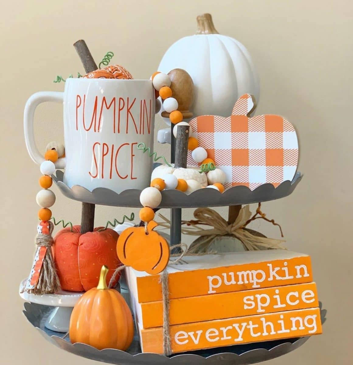 Halloween tiered tray ideas for home.  Orange and white plaid pumpkins, pumpkin spice mug, orange and white wooden beads, pumpkin spice everything wooden books, and two tiered tray