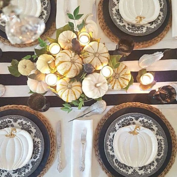 Halloween Table Decorations by Ciao Newport Beach with a black and white pumpkin filled table