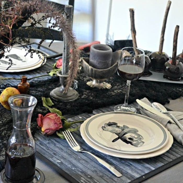 Halloween Table Decorations by Red Cottage Chronicles with skeleton, candles and candy apples as part of the table setting