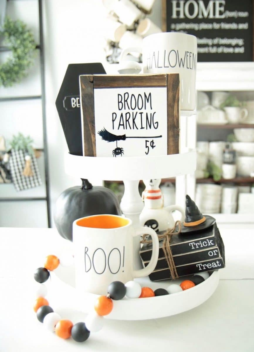 Halloween tiered tray ideas for home.  Witches broom parking sign, wooden black books that say Trick or Treat, Rae Dunn mugs and pumpkins.