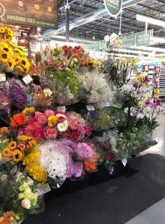 Best places to buy flowers showing a the display at Whole Foods. Gerber daisies, white daisies, babies breath, roses, sunflowers, and more.
