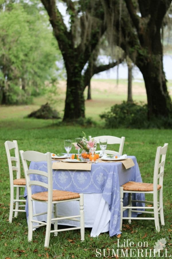 How to create a candle from an orange for a beautiful tablescape outdoor party.  Table with light blue table cloth, white chairs, crystal and china, tropical floral arrangement centerpiece and candle oranges made with tea light.