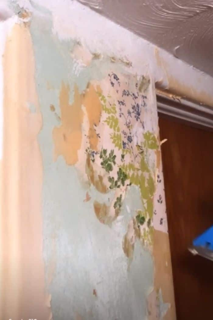 how to remove wallpaper with a steamer.  Removing old wallpaper and finding six different wallpapers in different spots under wallpaper.