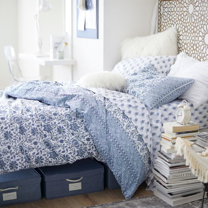 College dorm decor ideas in a pottery barn blue and white paisley comforter set.  Bed is sitting on white painted crates inside a white bedroom.  Ladder on the wall, desk under a window with white paper tassel garland and white industrial lamp.