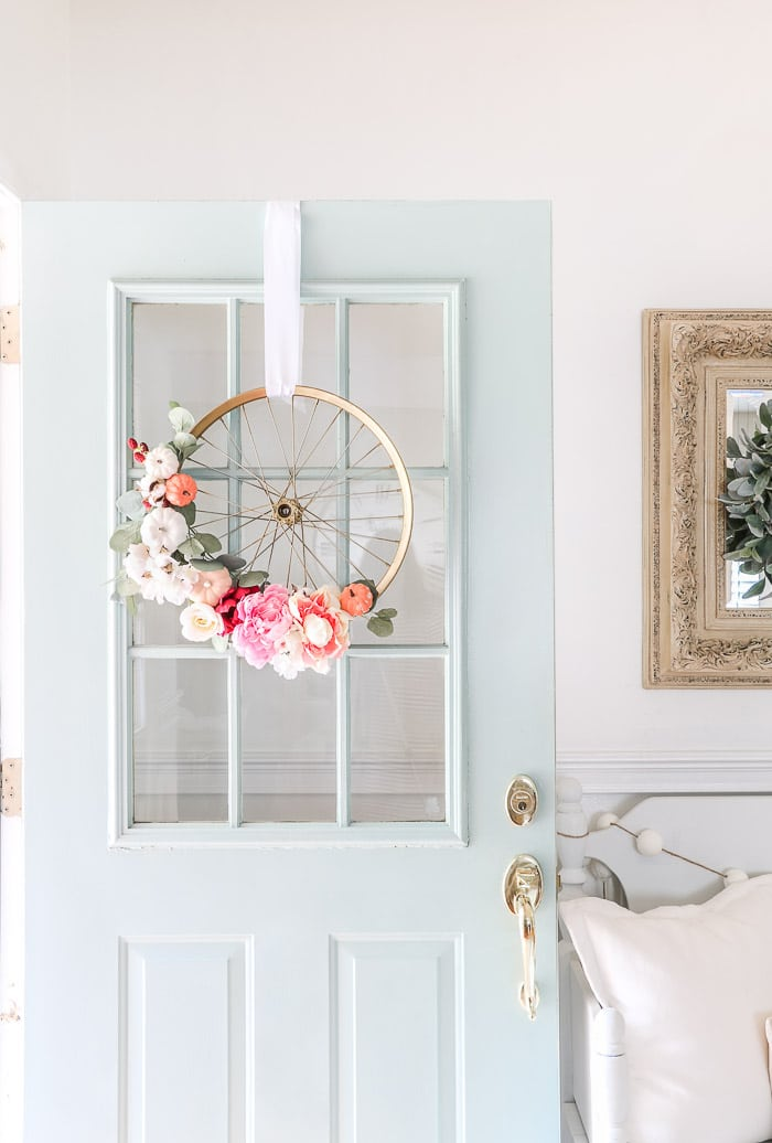 How to hang a wreath with ribbon. This old child's bicycle has been transformed into a beautiful bright and cheery fall wreath.  Using a gold frame bike wheel, white, pink and orange pumpkins, pink and white flowers and eucalyptus leaves.