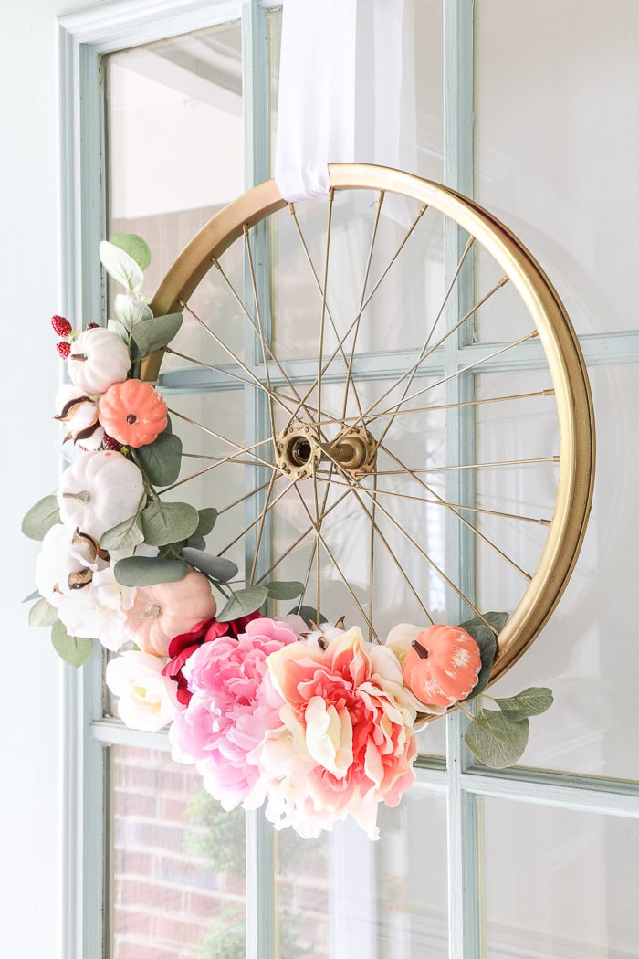How to hang a wreath with ribbon on a front door featuring my bicycle fall wreath decorated with white and pink pumpkins, flowers, berries and eucalyptus leaves.